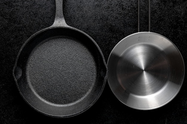 Overhead shot of two metal frying pans on a black background Free Photo