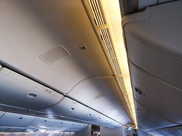 Overhead storage in passenger cabin on airplane. background concept for transportation and travel Premium Photo