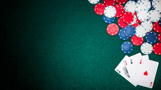 Overhead view of aces and casino chips on green poker table Free Photo