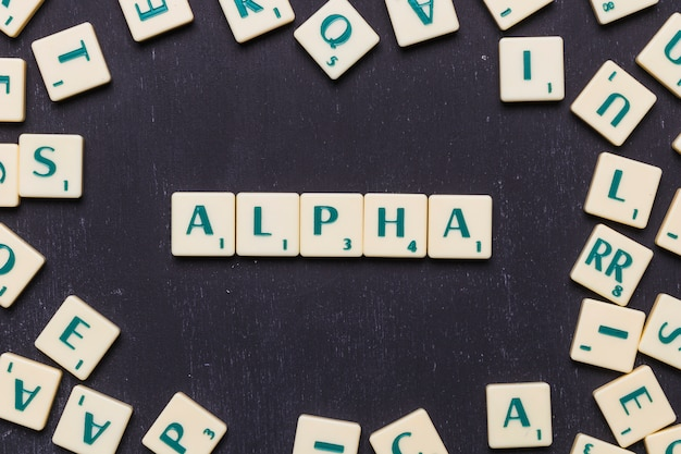 Overhead view of alpha text on scrabble letters over black backdrop Free Photo