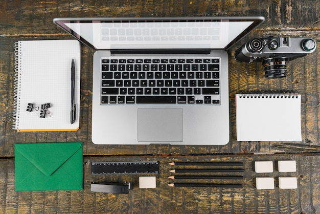 Overhead view of arranged office stationeries and laptop; retro camera on wooden desk Free Photo