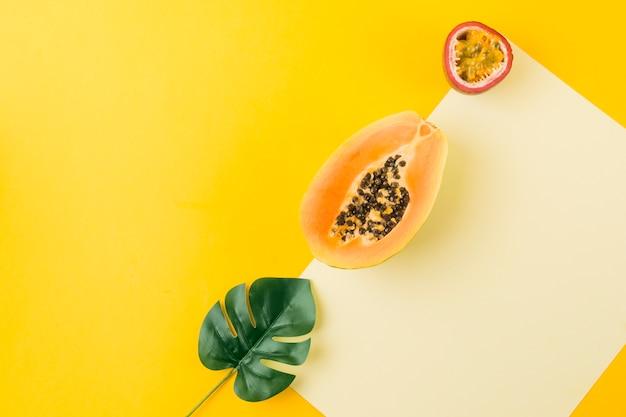 Una vista dall'alto di foglia artificiale; papaya e frutto della passione su carta bianca contro sfondo giallo Foto Gratuite