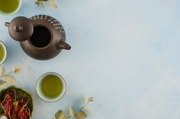 An overhead view of asian traditional teapot and teacups with herbs on white background Free Photo