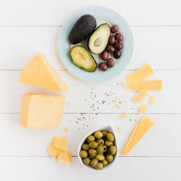An overhead view of avocado; olives and cheese chunk on white table Free Photo
