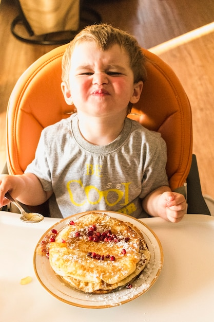 Overhead view of baby boy pouting while eating pancake Free Photo