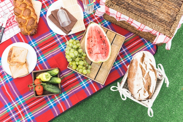 An overhead view of baked bread; fruits and picnic basket on blanket Free Photo