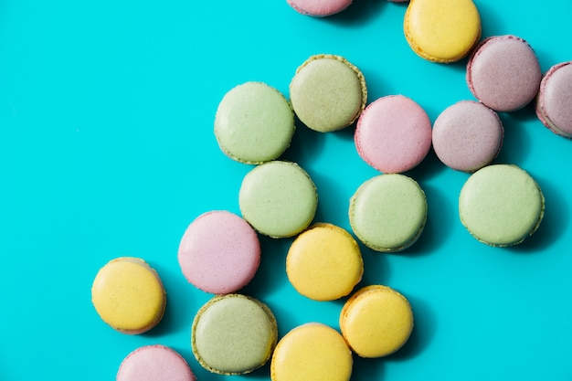 An overhead view of baked green; yellow and pink macaroons on blue background Free Photo
