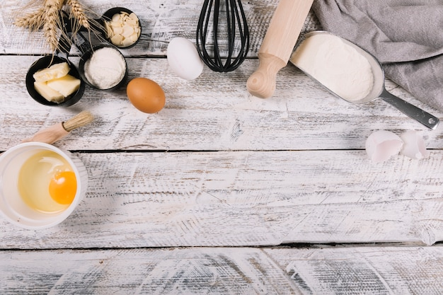 An overhead view of baked ingredients on white wooden table Free Photo