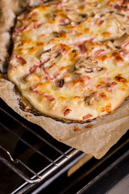 An overhead view of baked pizza over the oven grate Free Photo