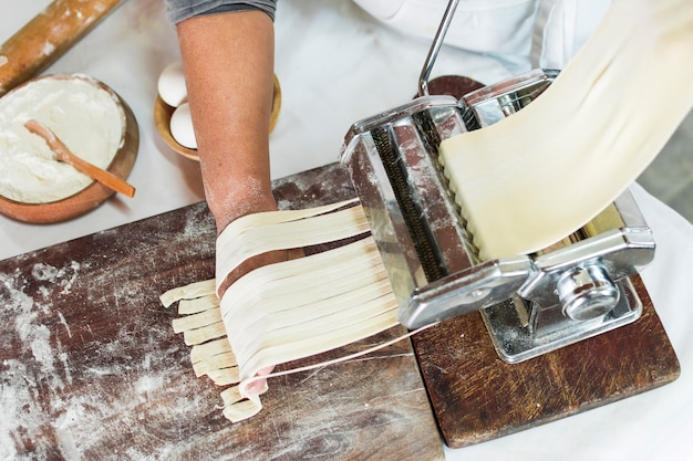 An overhead view of baker cutting raw dough into tagliatelle on pasta machine Free Photo
