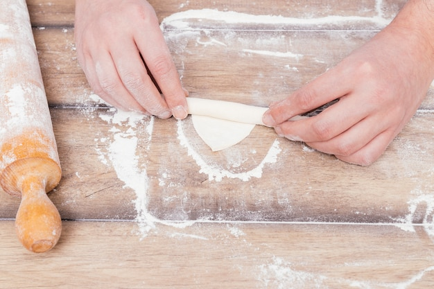 An overhead view of a baker's hand rolling the dough on flour over the table Free Photo