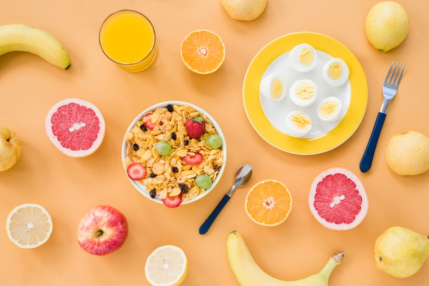 An overhead view of banana; grapefruit; orange; pears; juice; boiled eggs and cornflakes on brown background Free Photo