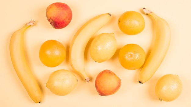 An overhead view of banana; peach; apple; oranges and lemons against beige background Free Photo