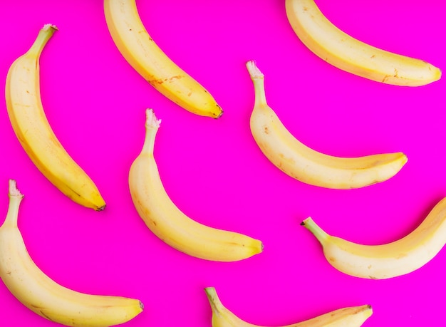 An overhead view of bananas on pink backdrop Free Photo