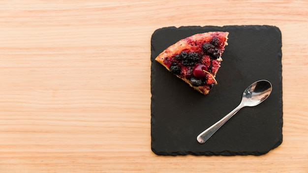 Overhead view of berry pastry and spoon on shale board Free Photo