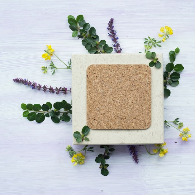 Overhead view of blank cork frame with lavender flowers and twig on wooden background Free Photo