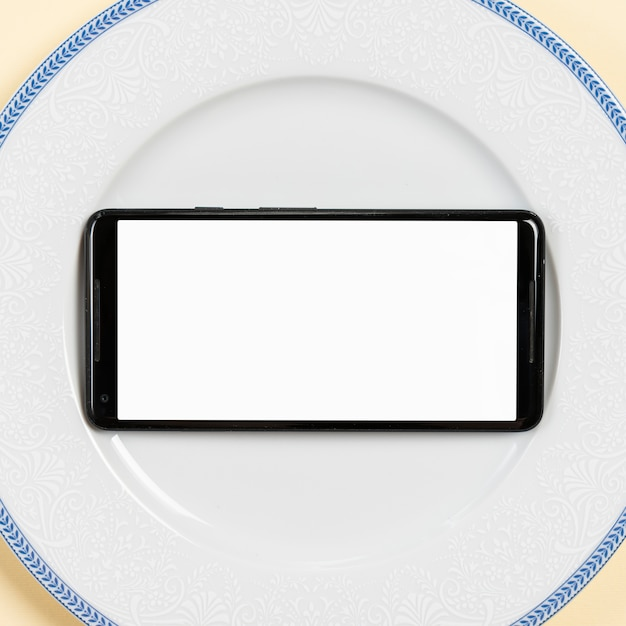 An overhead view of blank screen mobile on white plate Free Photo
