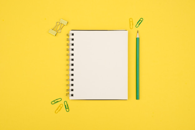 Overhead view of blank spiral notepad with pencil and paperclip over yellow surface Free Photo