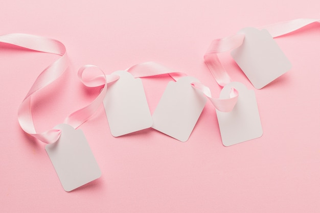 Overhead view of blank tags and pink ribbon against plain pink backdrop Free Photo