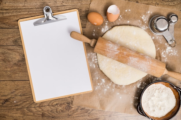 An overhead view of blank white paper on clipboard with flat dough ready for baking on parchment paper over the wooden table Premium Photo