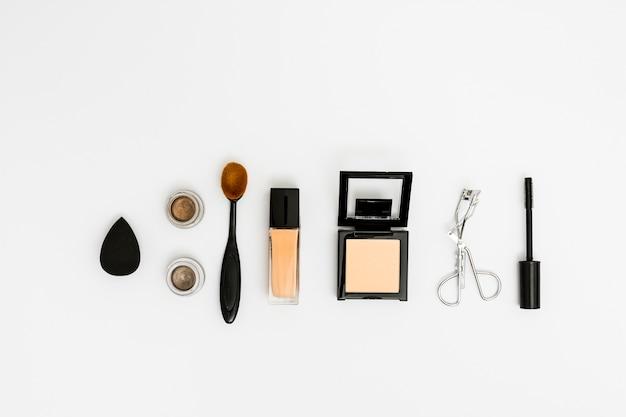 An overhead view of blender; eyeshadow; oval brush; compact powder; eyelash curler and mascara brush on white backdrop Free Photo