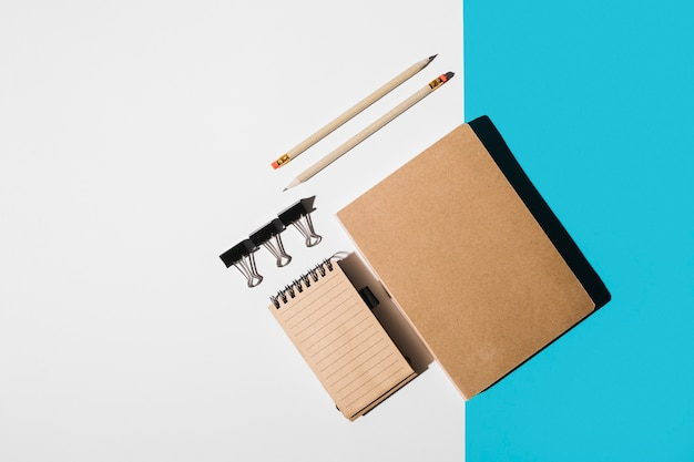An overhead view of book; spiral notepad; pencil; bulldog clips on white and blue backdrop Free Photo