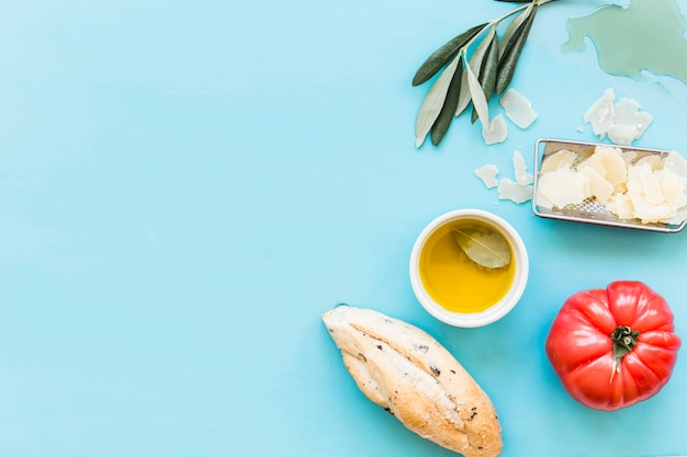 Overhead view of bread, oil, grated cheese and tomato on blue background Free Photo