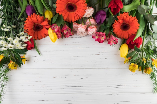 An overhead view of bright colored flowers on white wooden table Free Photo