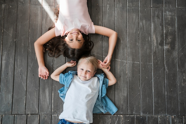 An overhead view of brother and sister lying on hardwood floor looking up Free Photo