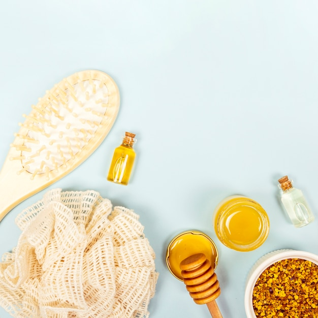 Overhead view of brush; essential oil bottle; honey jar; bee pollen and loofah Free Photo