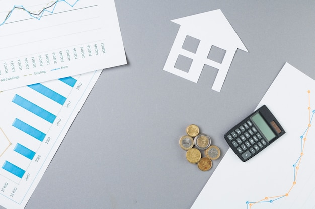 Overhead view of business desk with stacked coins; calculator; house cutout and graph Free Photo