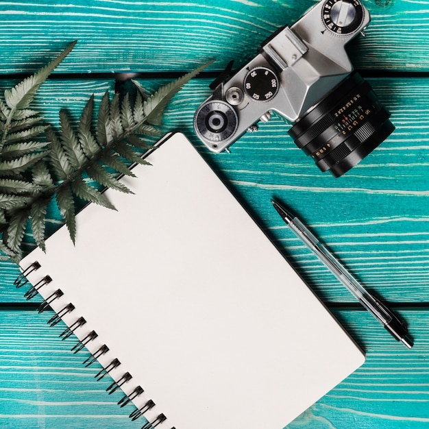 An overhead view of camera; fern; pen and blank spiral notepad on wooden textured background Free Photo