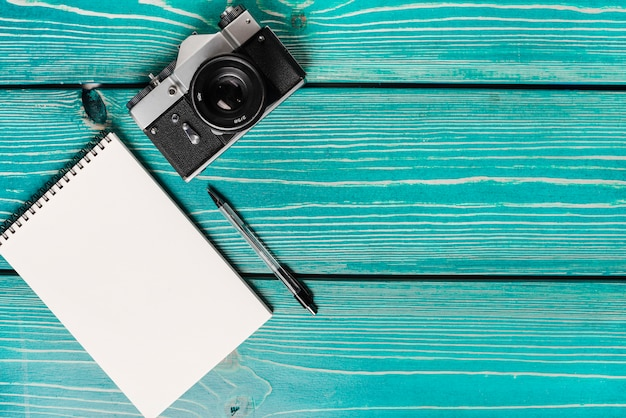 An overhead view of camera; spiral notepad and pen on wooden plank Free Photo