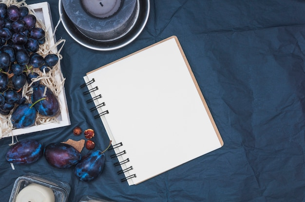 An overhead view of candles; blank spiral notepad; plums and grapes on textile backdrop Free Photo