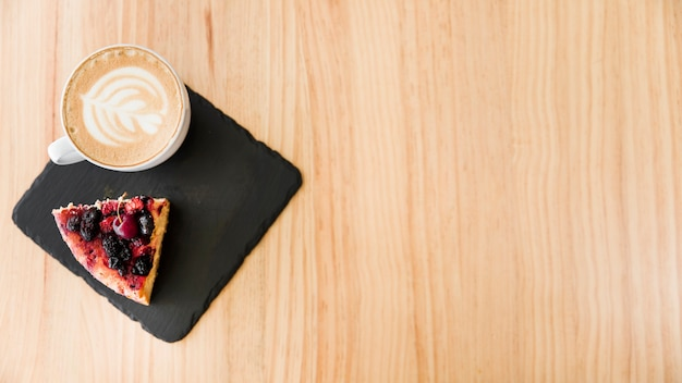 An overhead view of cappuccino coffee with art latte and cake slice on wooden backdrop Free Photo