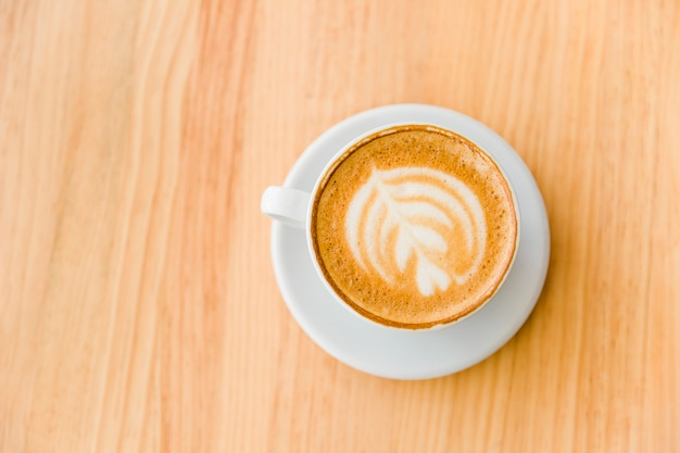 An overhead view of cappuccino coffee with art latte on wooden table Free Photo