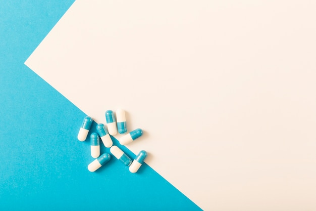 Overhead view of capsules over the white and blue backdrop Premium Photo
