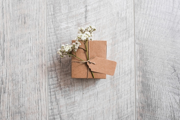 An overhead view of cardboard box tied with tag and baby's-breath flowers on wooden desk Free Photo