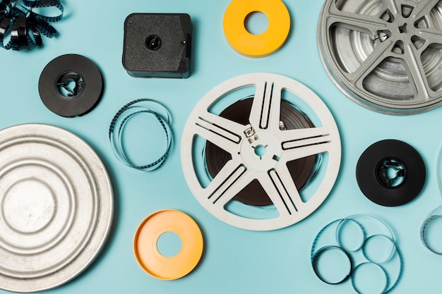 An overhead view of cases; filmstrips and film reels on blue background Free Photo