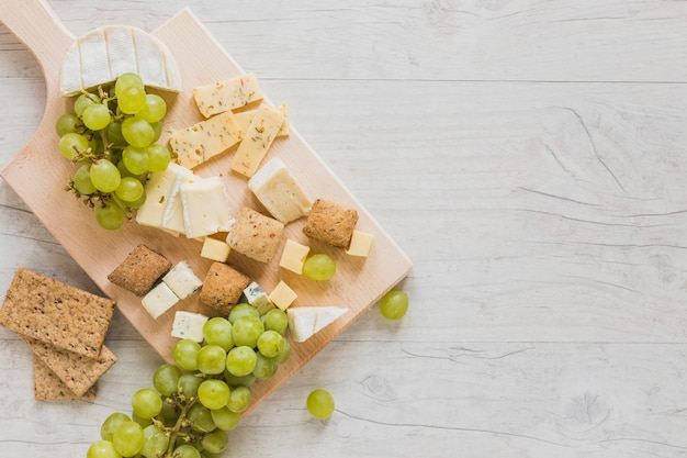 An overhead view of cheese blocks, crisp bread and grapes on wooden desk Free Photo