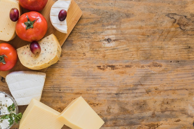 An overhead view of cheese blocks, grapes and tomatoes on wooden desk Free Photo