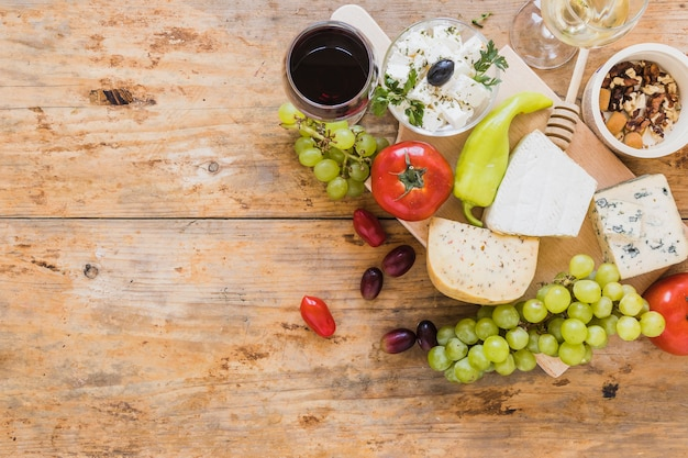 An overhead view of cheese blocks with grapes; tomatoes; green chili pepper and dried fruits Free Photo