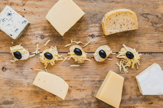 An overhead view of cheese blocks with mini sandwiches on wooden surface Free Photo