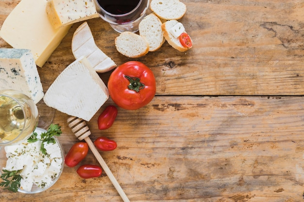 An overhead view of cheese blocks with tomatoes and bread on wooden backdrop Free Photo