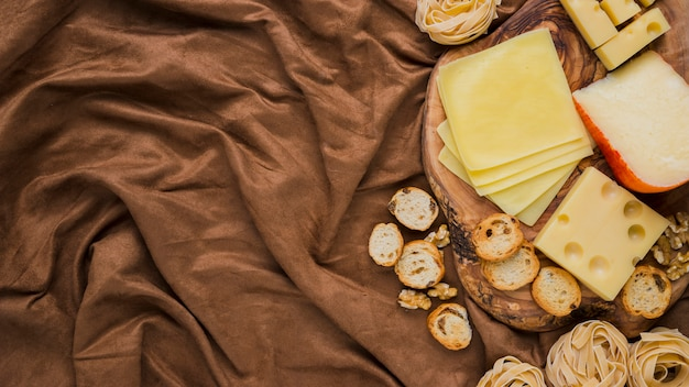 Overhead view of cheese, pasta and bread on crushed textile Free Photo
