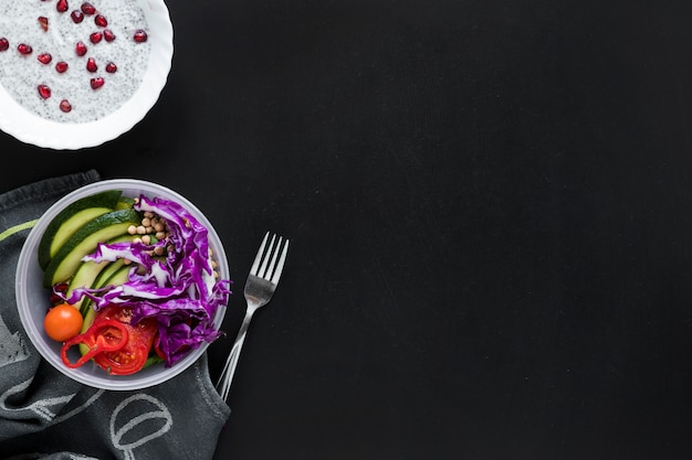 An overhead view of chia seed pudding and fresh vegetables salad over black background Free Photo