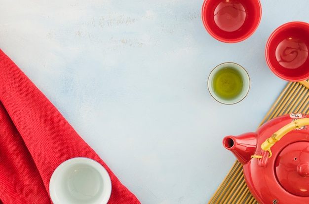 An overhead view of chinese teapot and teacups on white background Free Photo