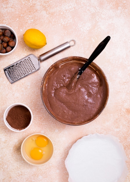 An overhead view of chocolate dough with ingredients on kitchen counter Free Photo