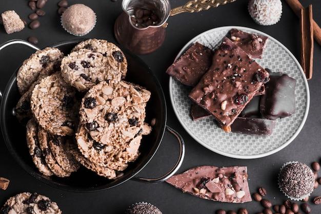 An overhead view of chocolate muesli cookies and truffles on black drop Free Photo
