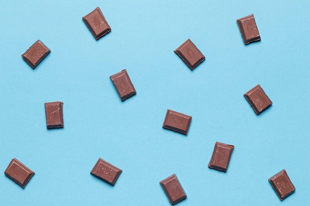 An overhead view of chocolate pieces on blue background Free Photo